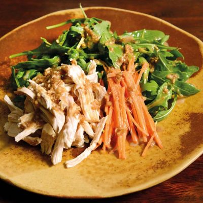 Chicken salad with rucula, carrot and homemade sesame sauce on top. Chicken is cooked at low temperature