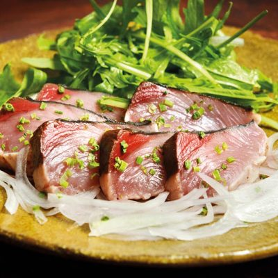 Salad with rucula, onion and tataki bonito (seared bonito), with homemade ponzu sauce