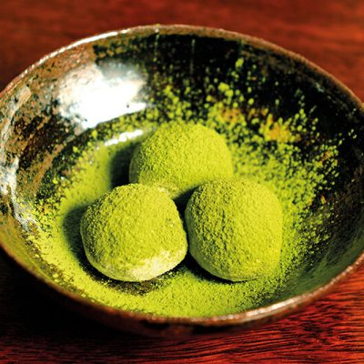 Homemade truffles made of black chocolate and a bit of sake covered with green tea powder
