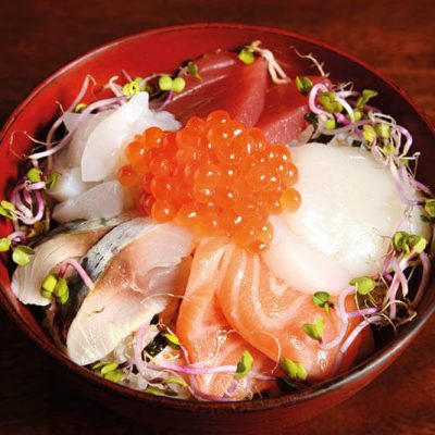 Big bowl of sushi rice with assorted sashimi such as tuna, salmon, horse mackerel, scallop, squid, salmon roe and radish sprout