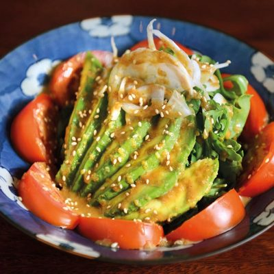Salad with rucula, avocado, tomato, onion and homemade sesame sauce on top
