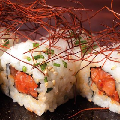 Uramaki filled with spicy salmon with spicy red pepper strings on top