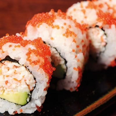 Uramaki filled with surimi, avocado, mayonnaise and flying fish roe eggs